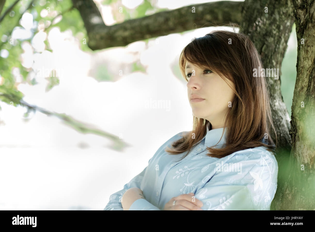 A woman leaning against a big tree alone in the park - Stock Image