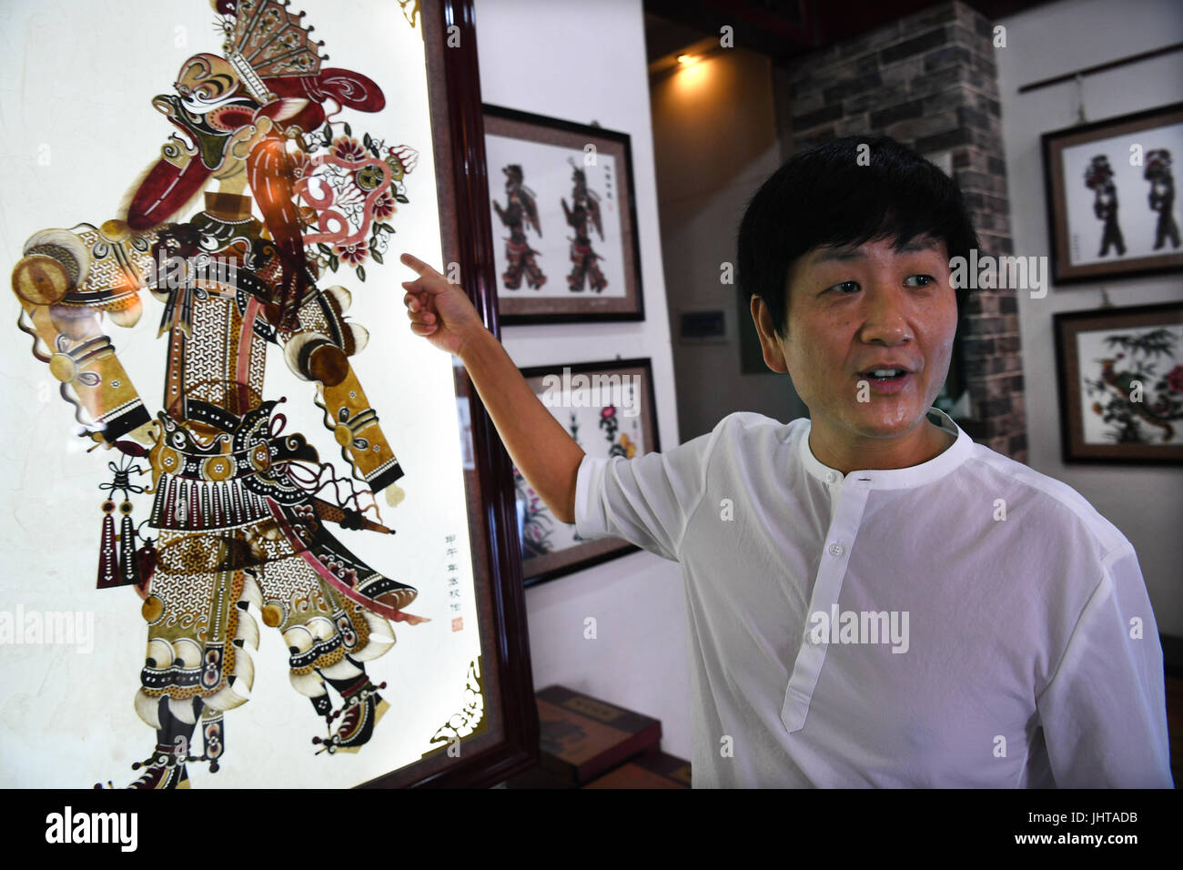 Xi'an, China's Shaanxi Province. 15th July, 2017. Shaddow puppet artist Xue Hongquan introduces his creation - Stock Image