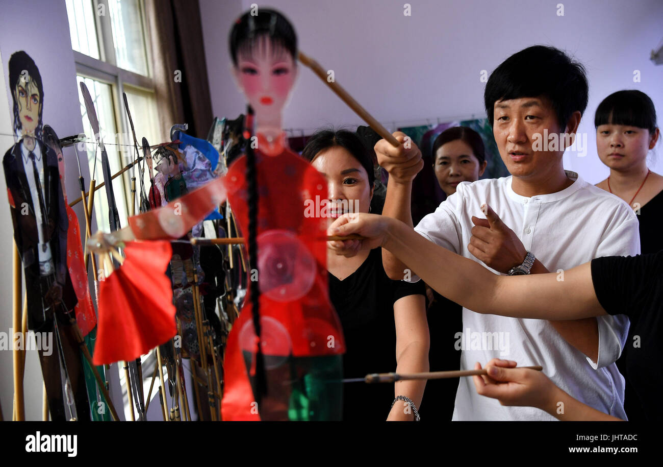 Xi'an, China's Shaanxi Province. 15th July, 2017. Shaddow puppet artist Xue Hongquan and other performers discuss Stock Photo