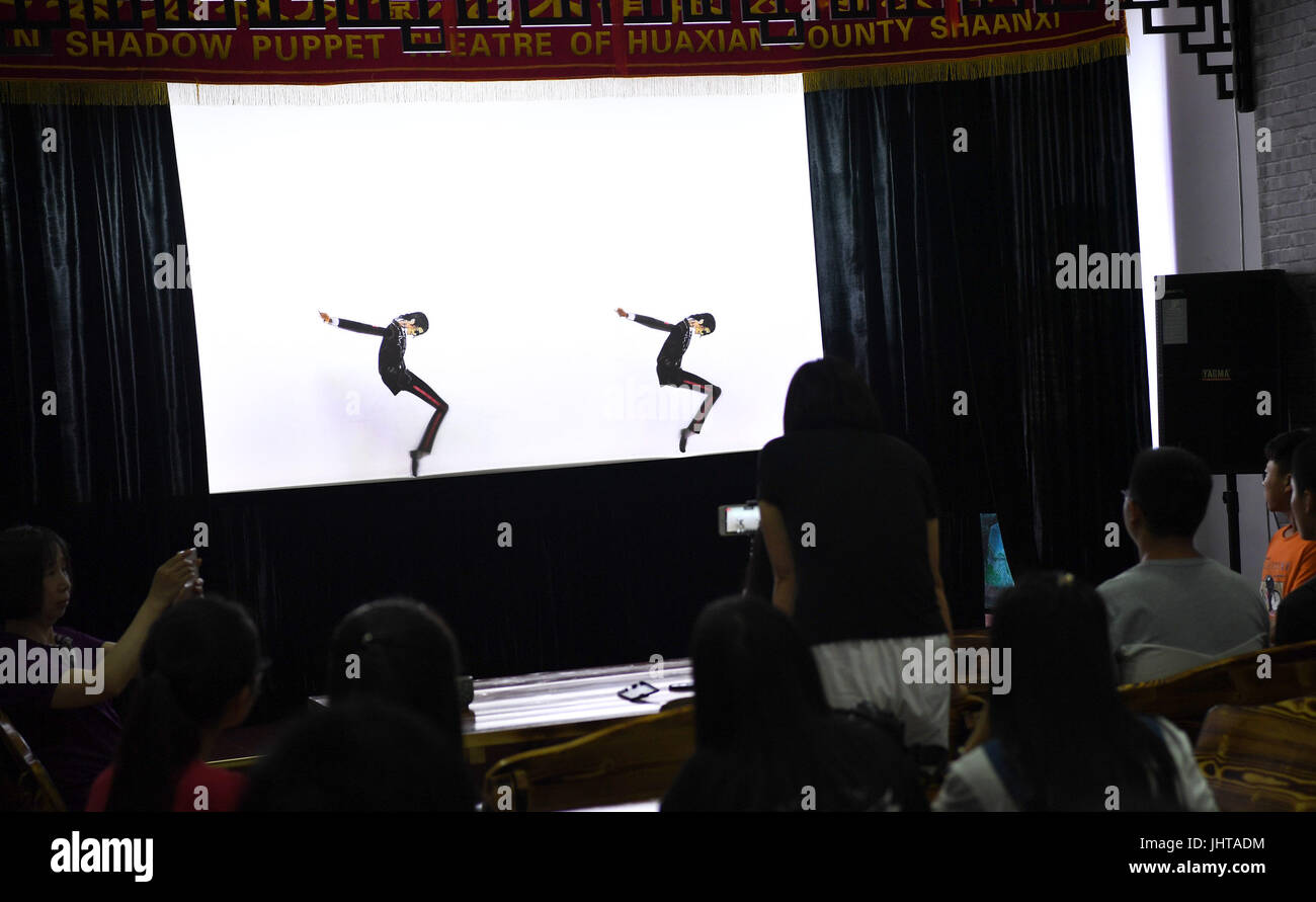 Xi'an, China's Shaanxi Province. 15th July, 2017. People watch shaddow puppets showing Michael Jackson's dance in Stock Photo