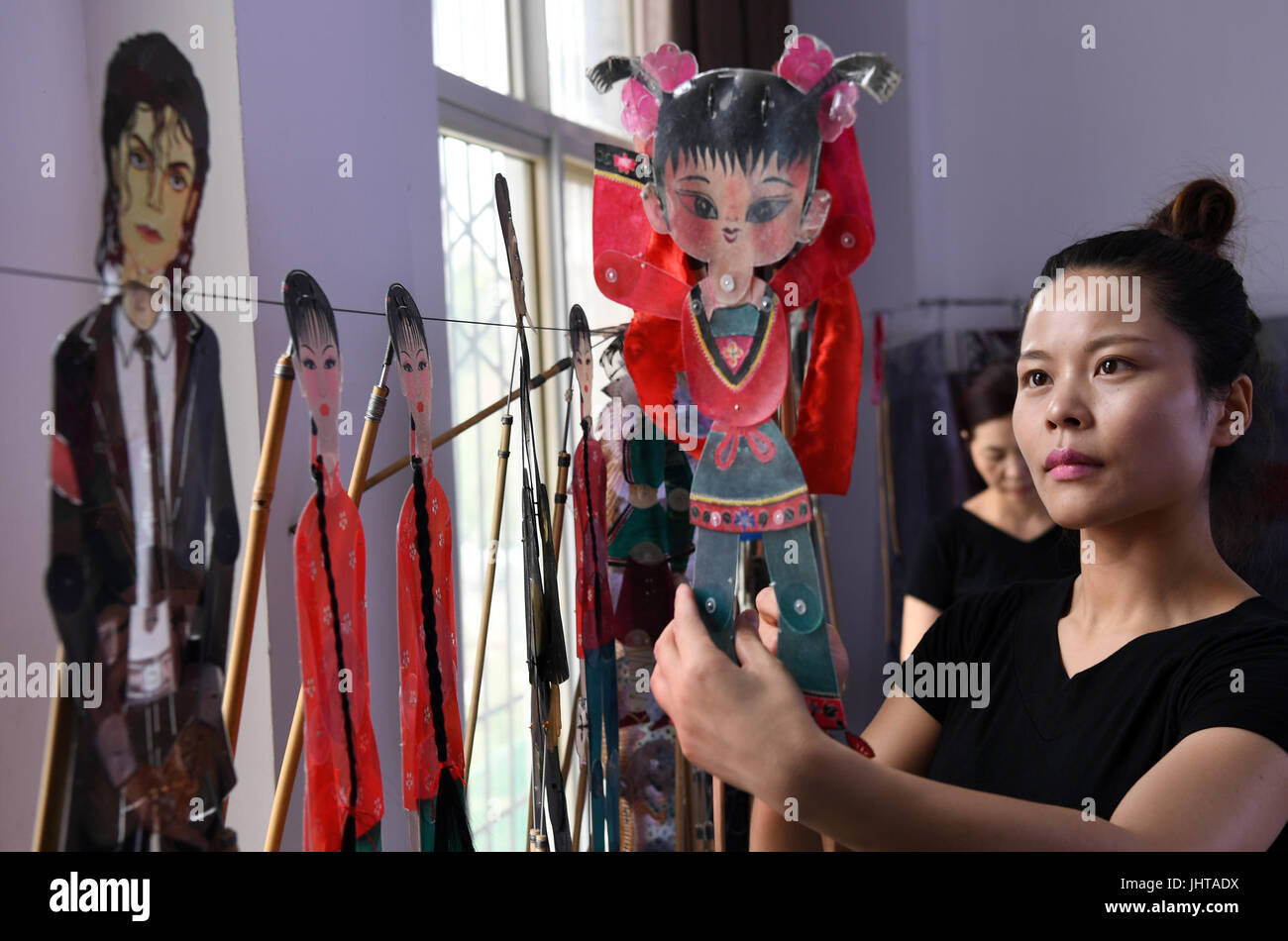 Xi'an, China's Shaanxi Province. 15th July, 2017. A performer holds a shaddow puppet in Xue Hongquan's theatre in Stock Photo