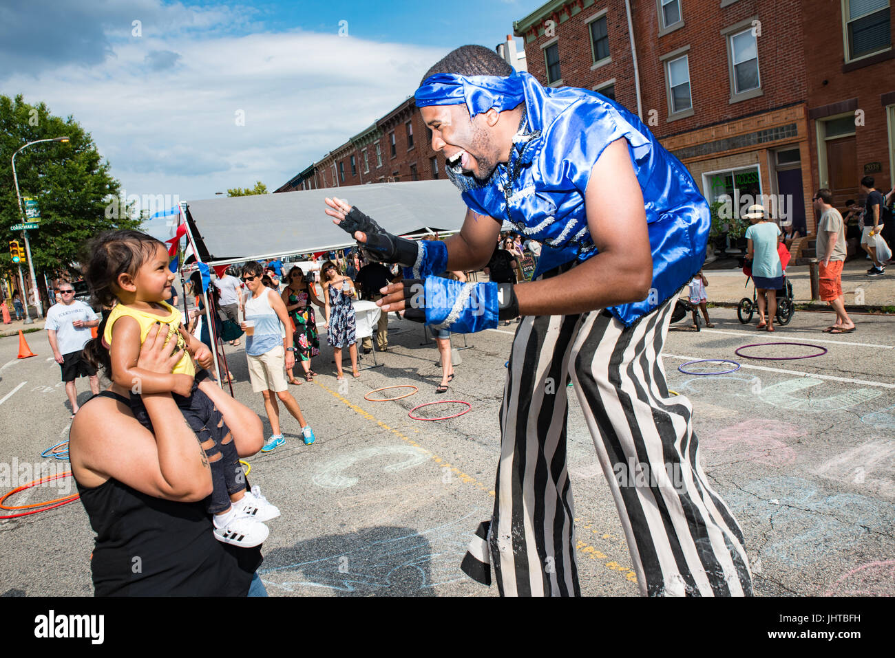 Philadelphia, USA. 15th July, 2017. Performer on stilts plays with a young child. Credit: Christopher Evens/Alamy - Stock Image
