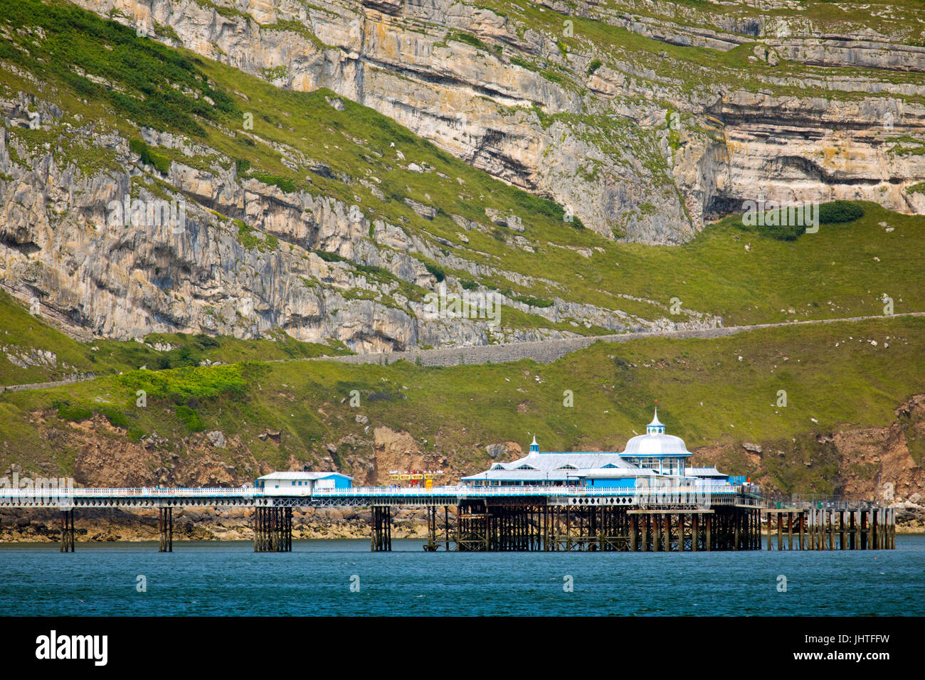 A summers day over both the Great Orme limestone rock formation and the Pier beneath it at the popular seaside resort Stock Photo