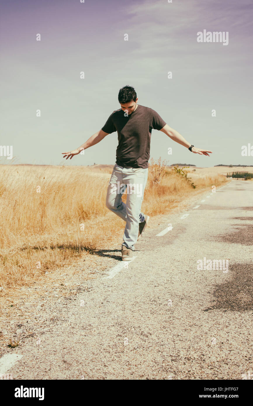 Young man walking an old road - Stock Image
