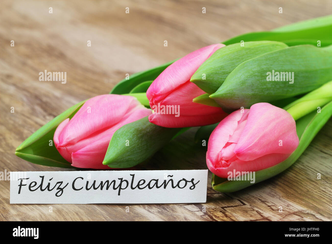 Feliz Cumpleanos Happy Birthday In Spanish Card With Pink Tulips On Wooden Surface