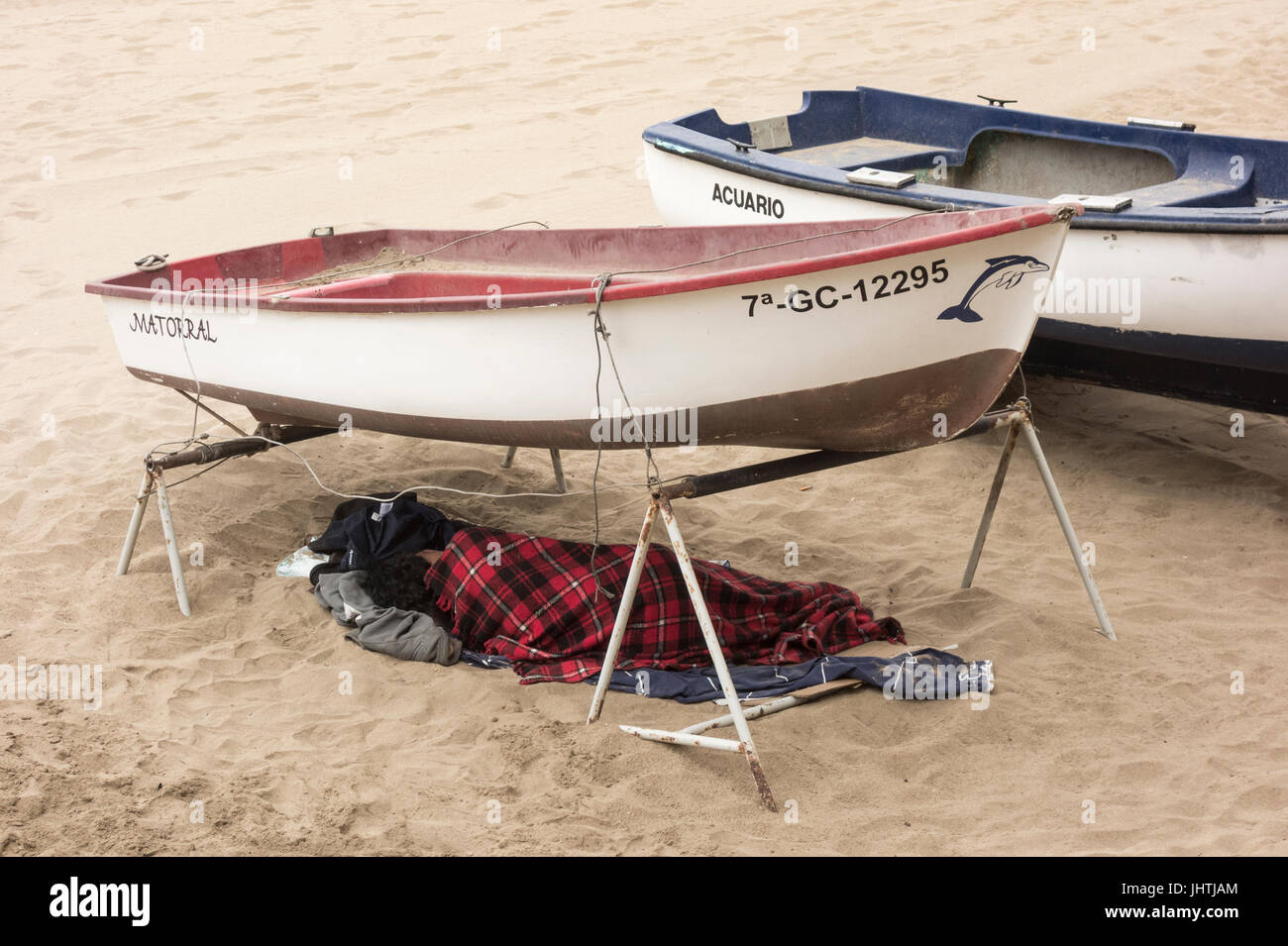 Homeless person sleeping under boat on beach in Spain - Stock Image