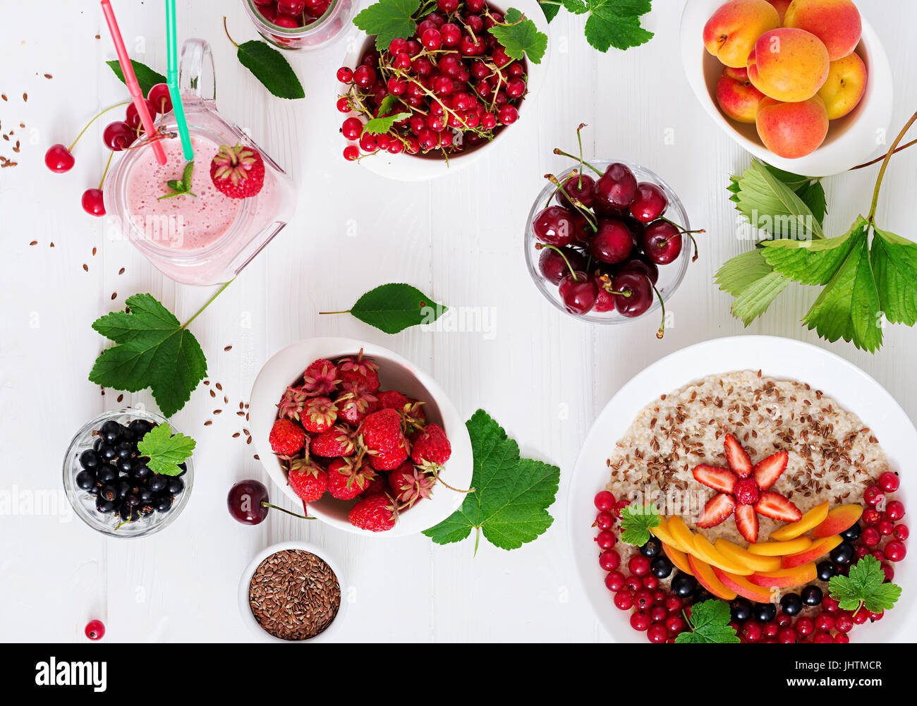 Tasty and healthy oatmeal porridge with berry, flax seeds and smoothies. Healthy breakfast. Fitness food. Proper Stock Photo