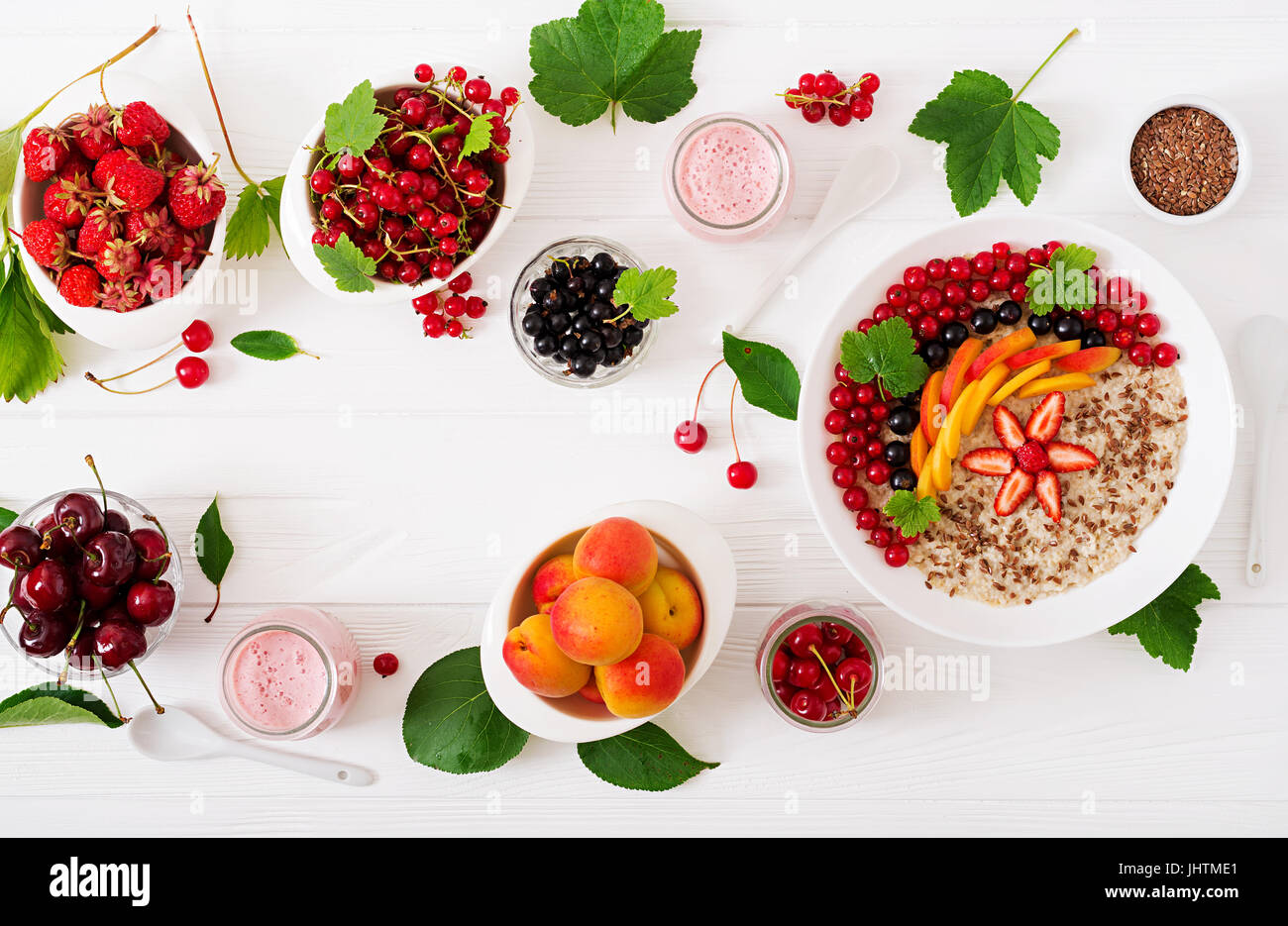 Tasty and healthy oatmeal porridge with berry, flax seeds and smoothies. Healthy breakfast. Fitness food. Proper - Stock Image