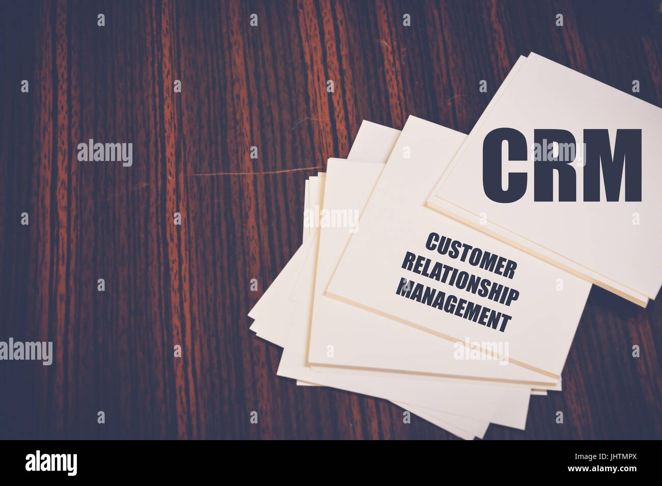 crm written on notepaper on wooden table, customer relationship management concept - Stock Image