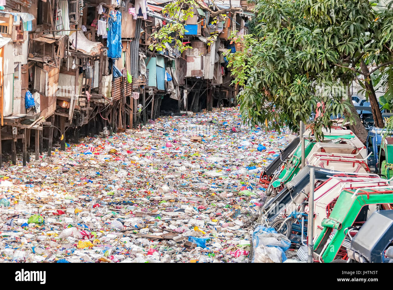 Shanties on stilts standing on garbage-filled river Stock Photo