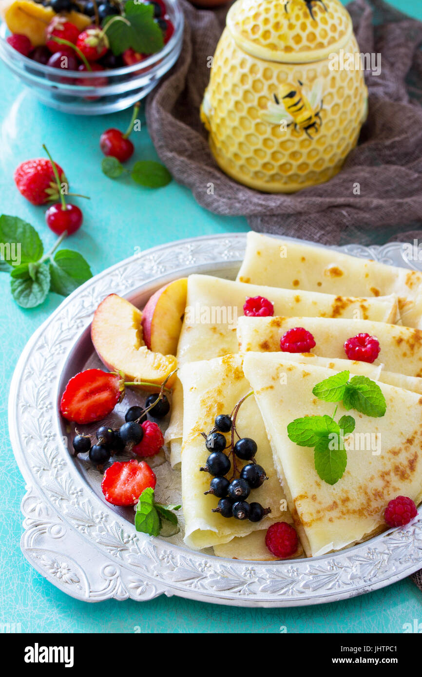 Pancakes with fresh berries of currants, strawberries, nectarines, sweet cherries and raspberries. - Stock Image