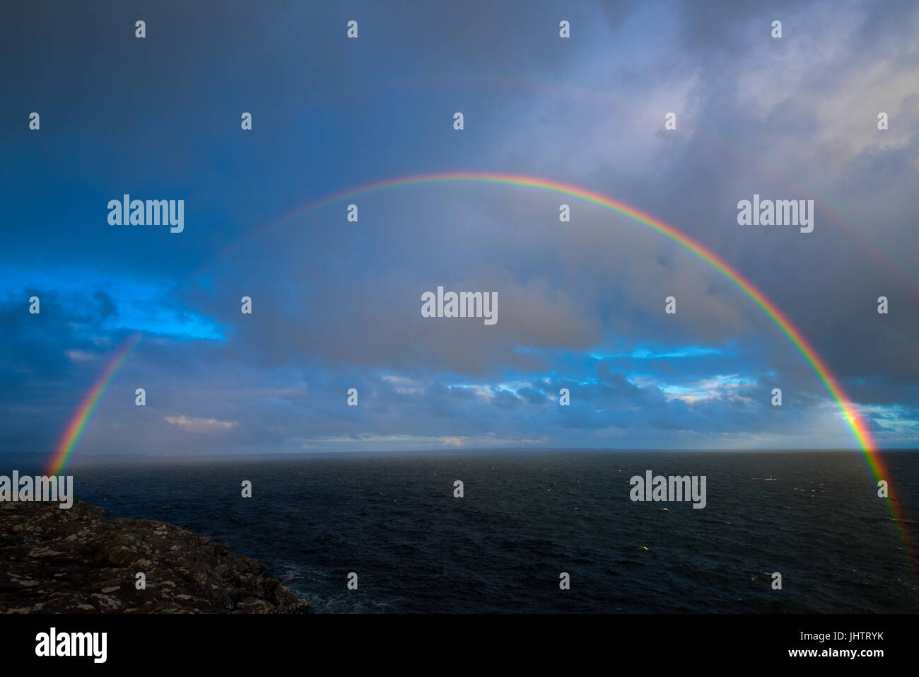 Rainbow  at  first-light  over  Ardnamurchan Point,  UK  mainland's most westerly point, Summer 2017 - Stock Image