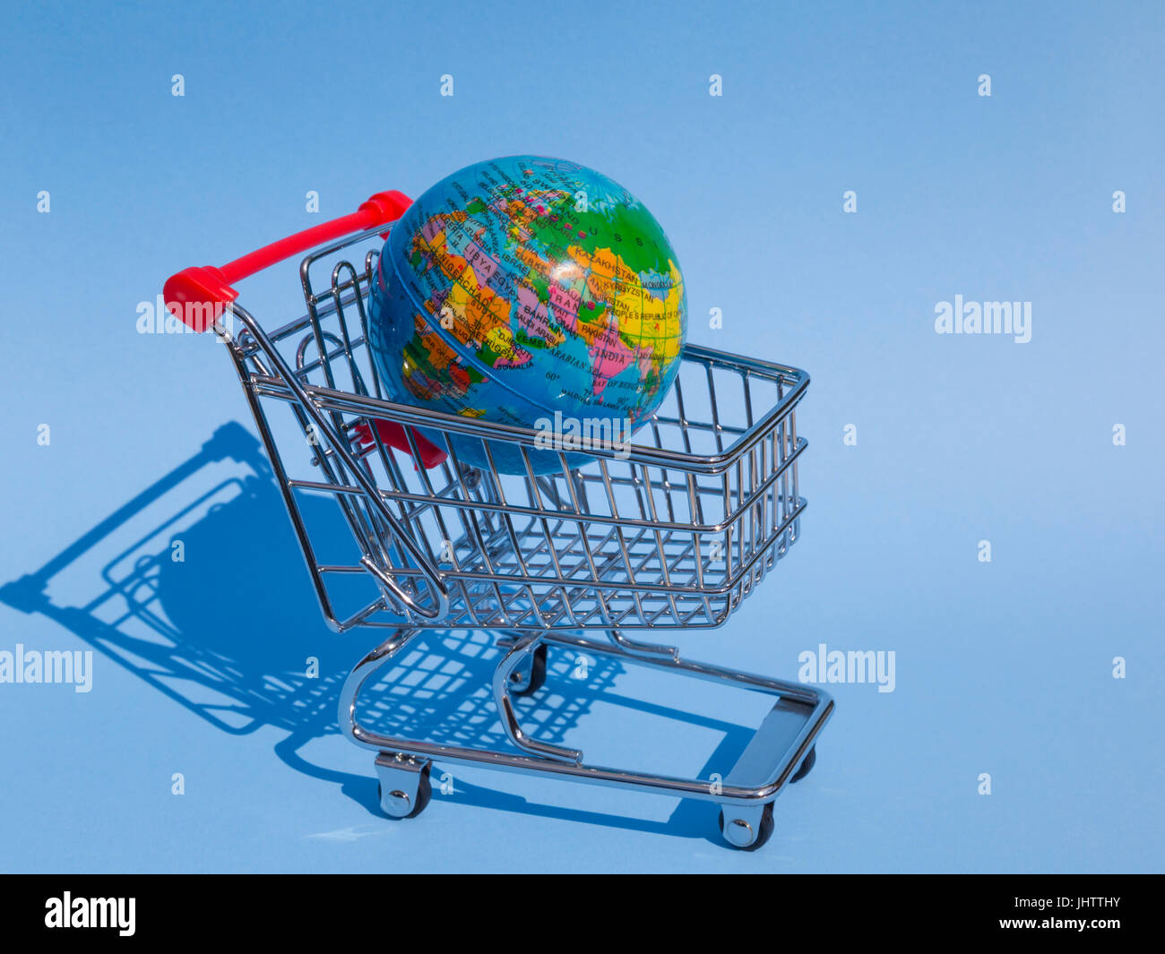 Shopping trolley with earth globe - Stock Image