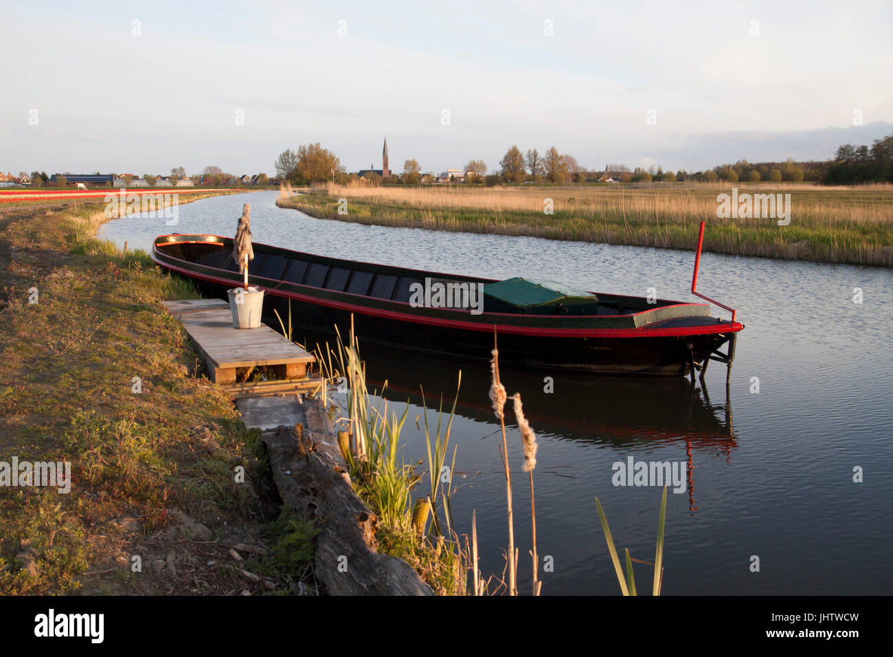 Picturesquely view of a rural scene of a ditch with an old steel heavy boat - Stock Image