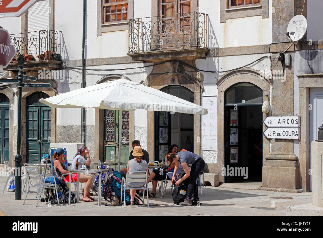 Young pilgrims walking Road to Santiago de Compostela take a break in a small cafe at Ponte de Lima Portugal - Stock Image