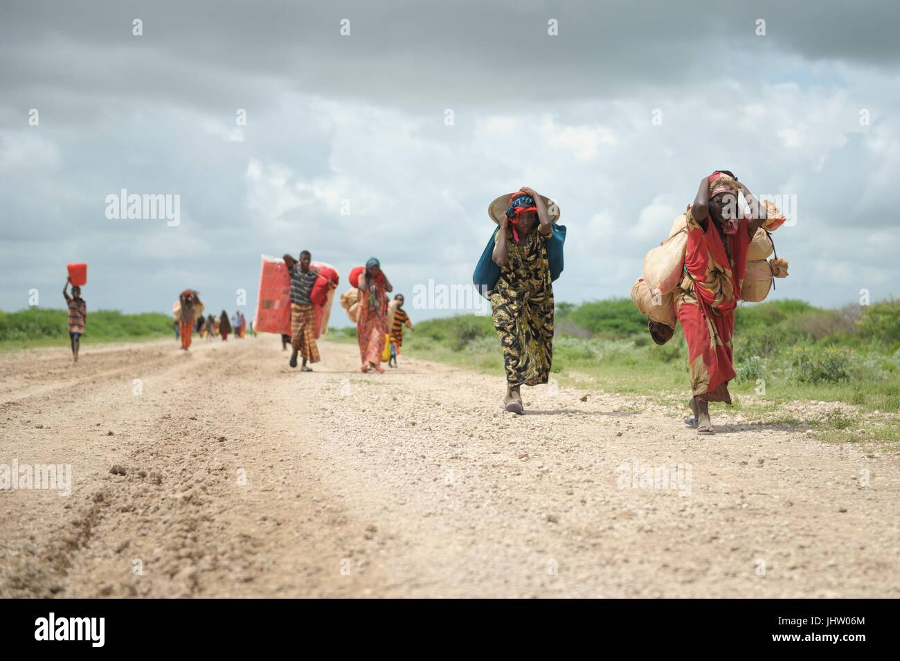 Somalian women carry their possessions to an IDP camp after being displaced by heavy rains November 12, 2013 in - Stock Image