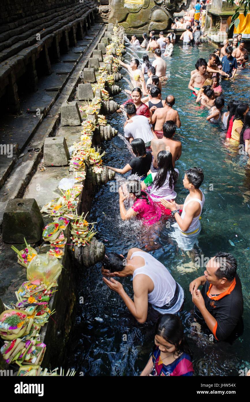 Balinese people in holy spring water of sacred pool at Pura Tirta Empul Temple, Tampaksiring, Bali, Indonesia - Stock Image