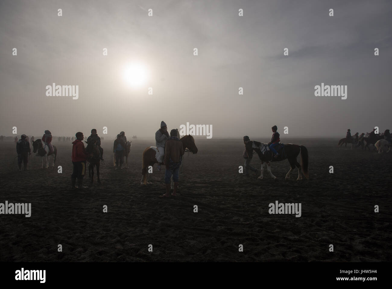 Indonesians horse riding in sea of sand in Mount Bromo East Java Indonesia. - Stock Image