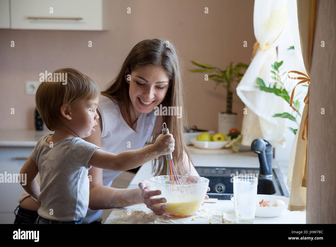 mother and young son prepare pie in the kitchen - Stock Image