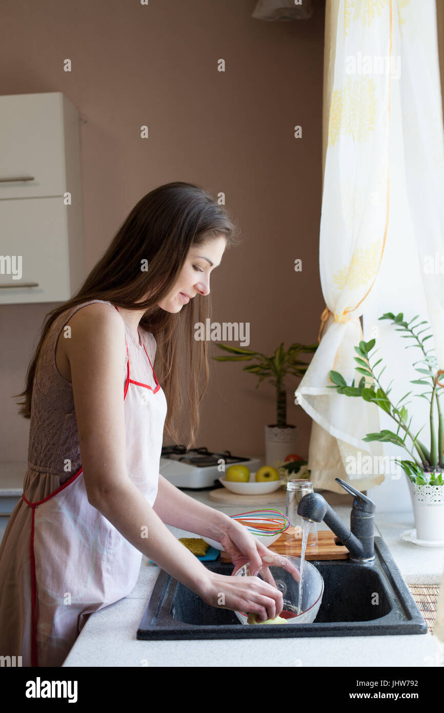 Girl Housewife Washes Dirty Dishes In The Kitchen