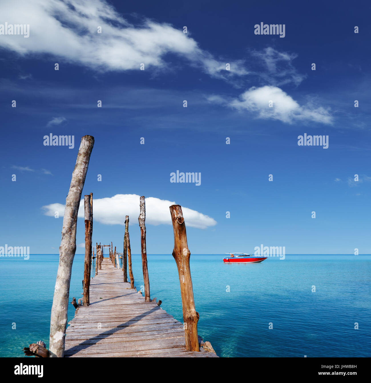 Wooden pier on a tropical island, sea and blue sky - Stock Image
