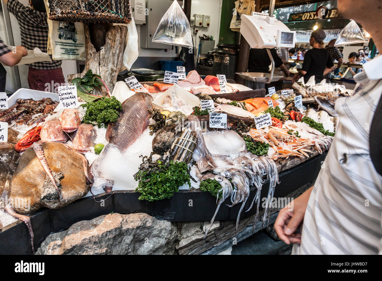 Customer at a wet fish stall in Borough Market, the historic food market in Southwark, central London, England, - Stock Image