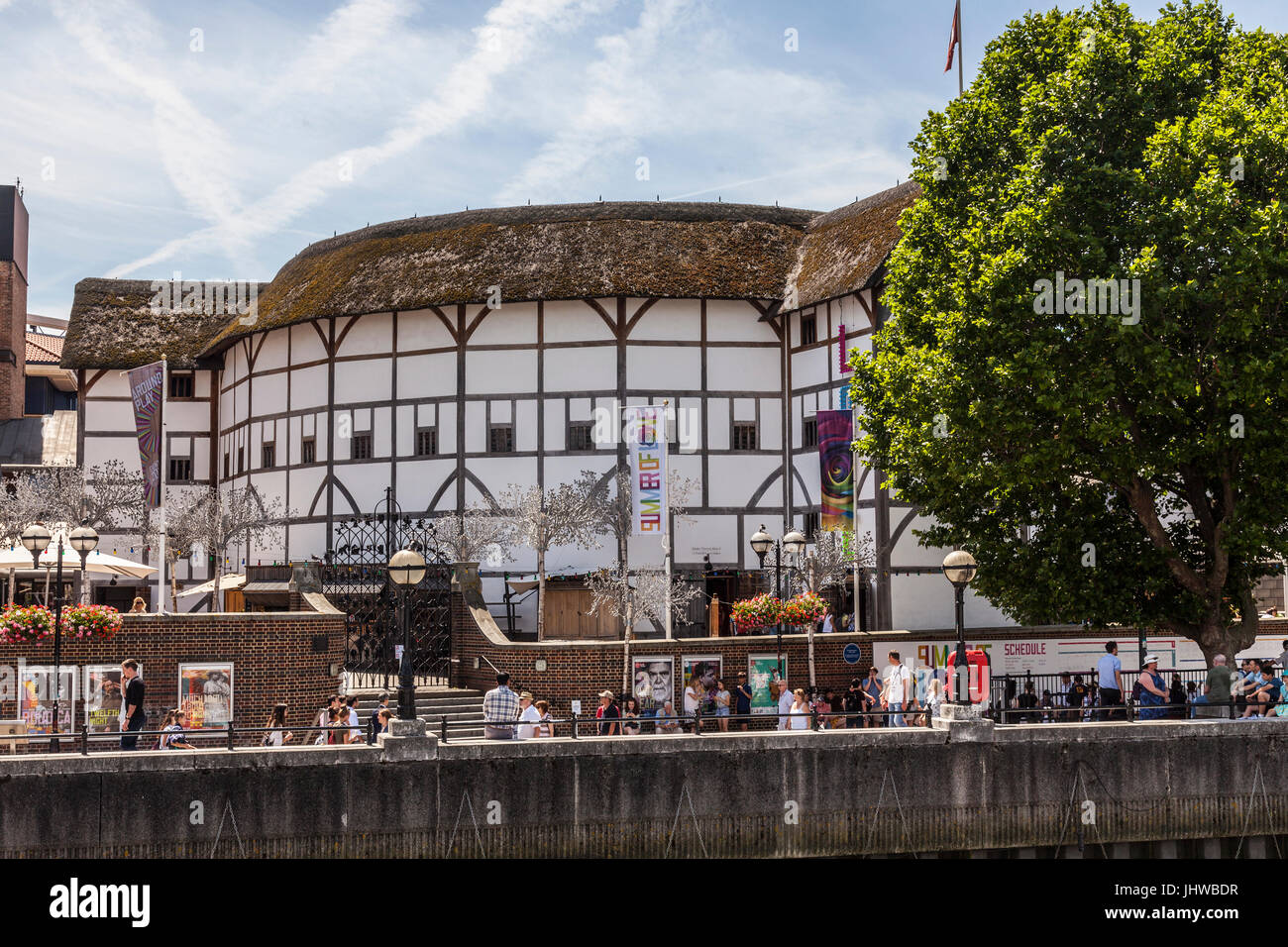 People on Bankside, the River Thames waterfront in front of Shakespeare's Globe Theatre, central London, on a hot Stock Photo