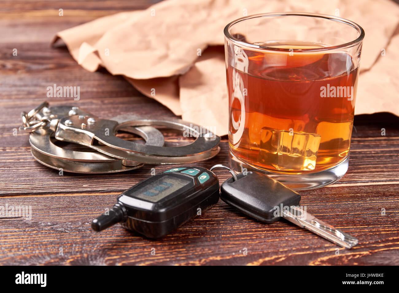 Handcuffs, car keys, whisky glass. - Stock Image