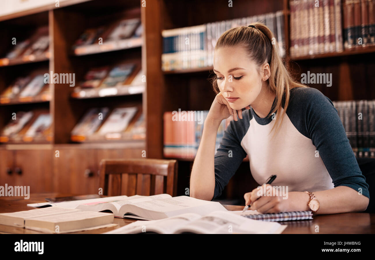 Young caucasian student learning from book in the library. College student making notes for exam in library. - Stock Image