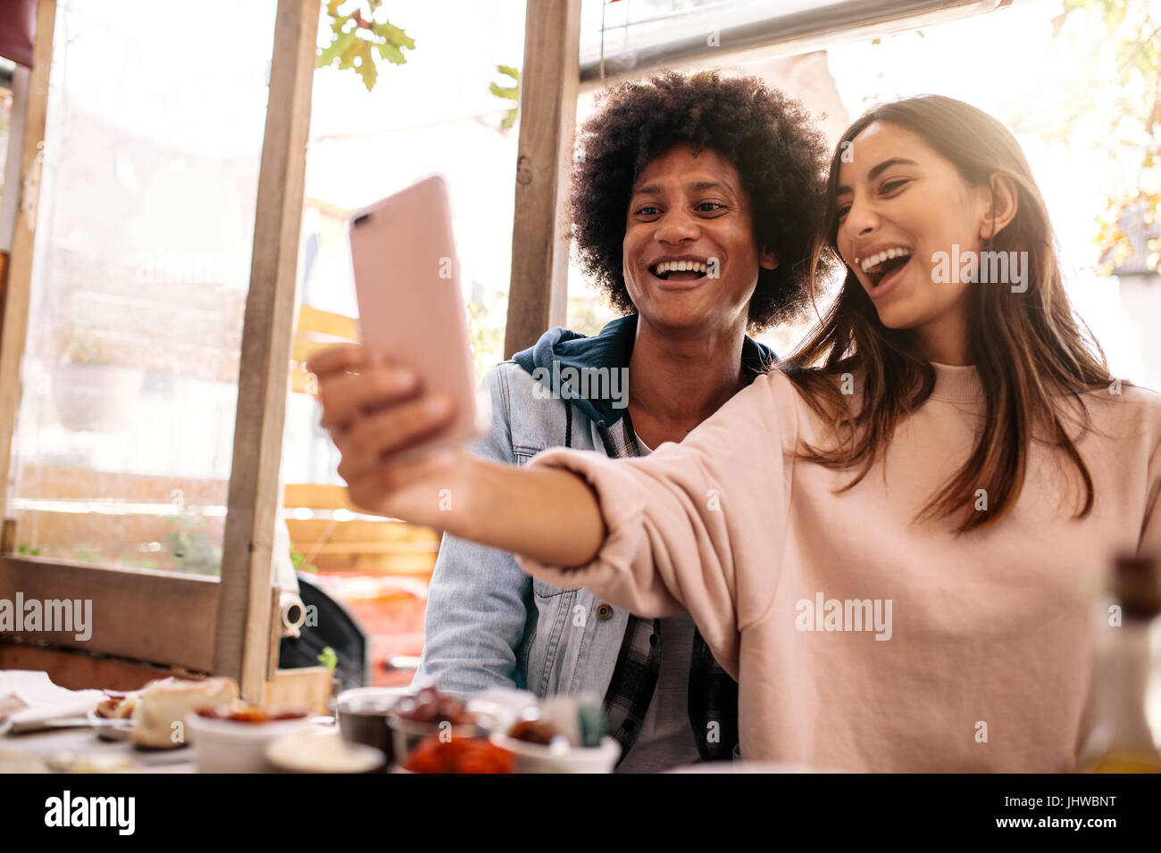 Young couple sitting in the cafe and taking selfie with smart phone. Beautiful woman taking self portrait with her - Stock Image