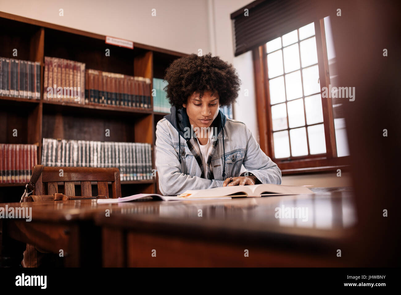 African college student reading book in library. Young student sitting at table in library and studying. - Stock Image