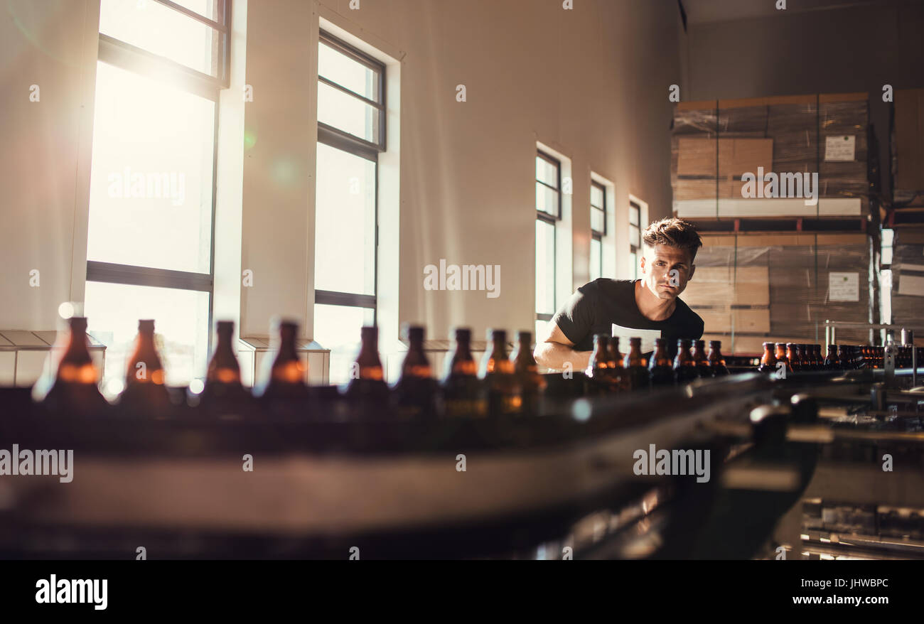 Brewer looking at conveyor with beer bottles. Young man supervising the manufacturing process of beer at brewery - Stock Image