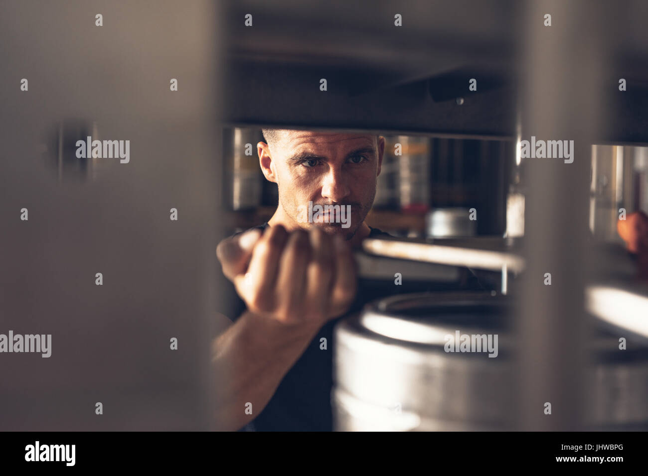Man working in brewery factory. Employee of production line putting aluminum keg on filling line. - Stock Image