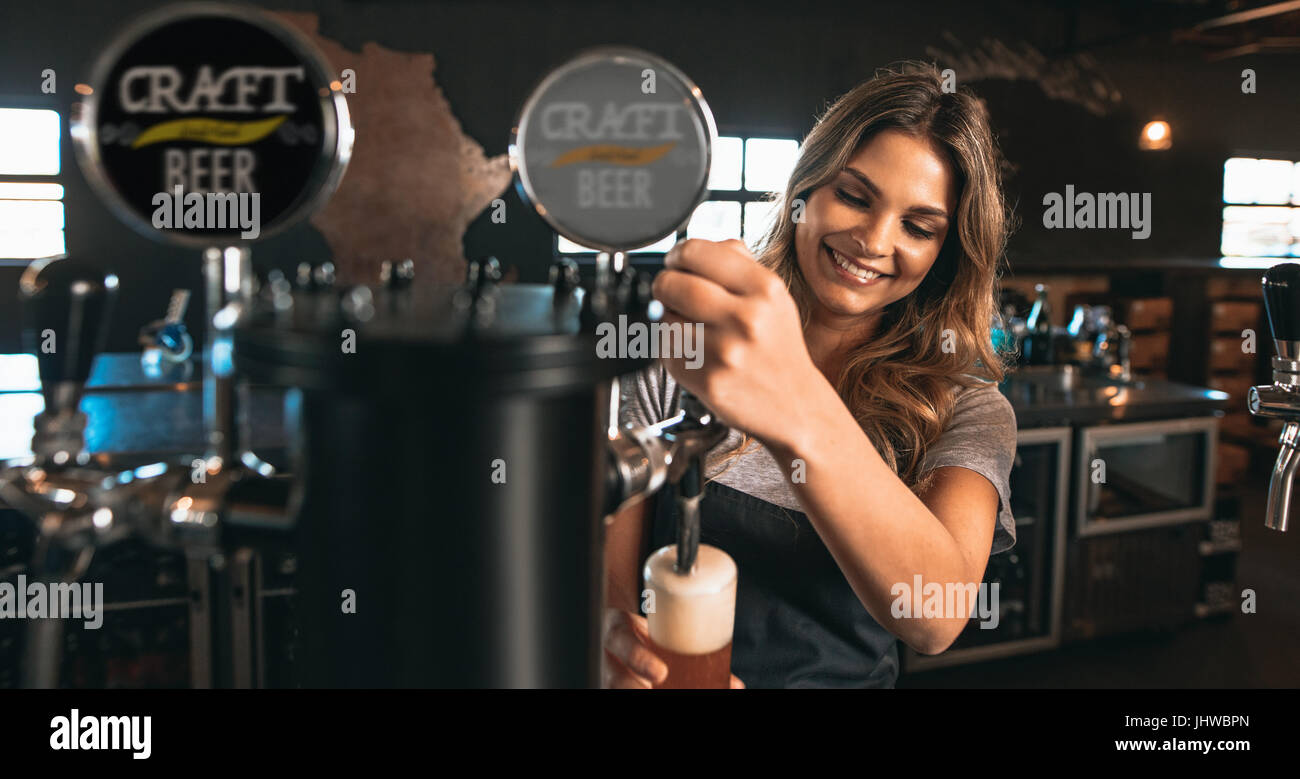 Beautiful young woman pouring beer into the glass. Female bartender tapping craft beer in bar. - Stock Image