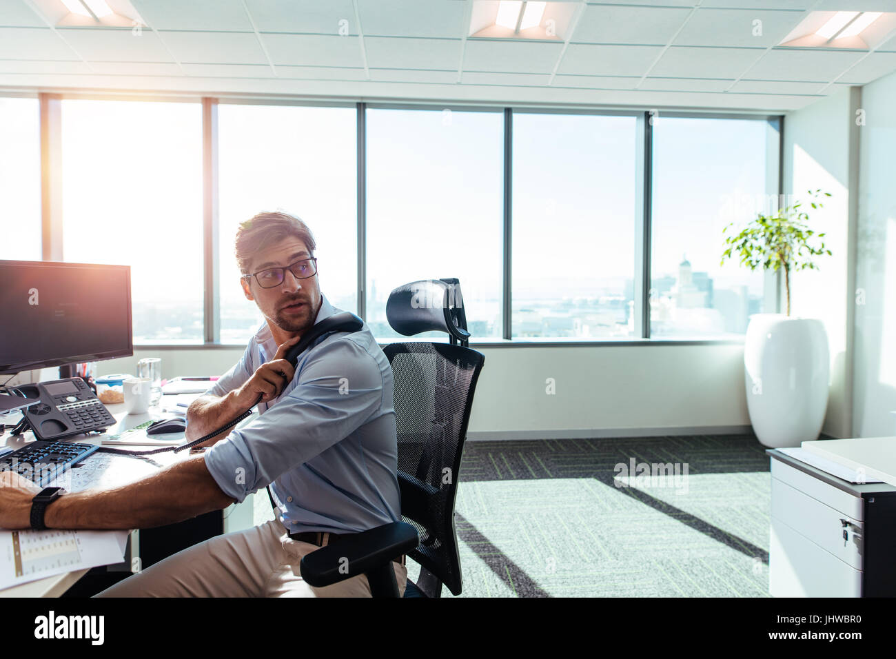 Businessman working in his office with computers and business papers on table. Young entrepreneur looking behind - Stock Image