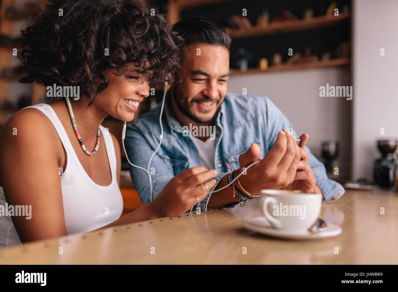 Happy young couple sitting at coffee shop having video chat on mobile phone. Young man and woman with earphones - Stock Image