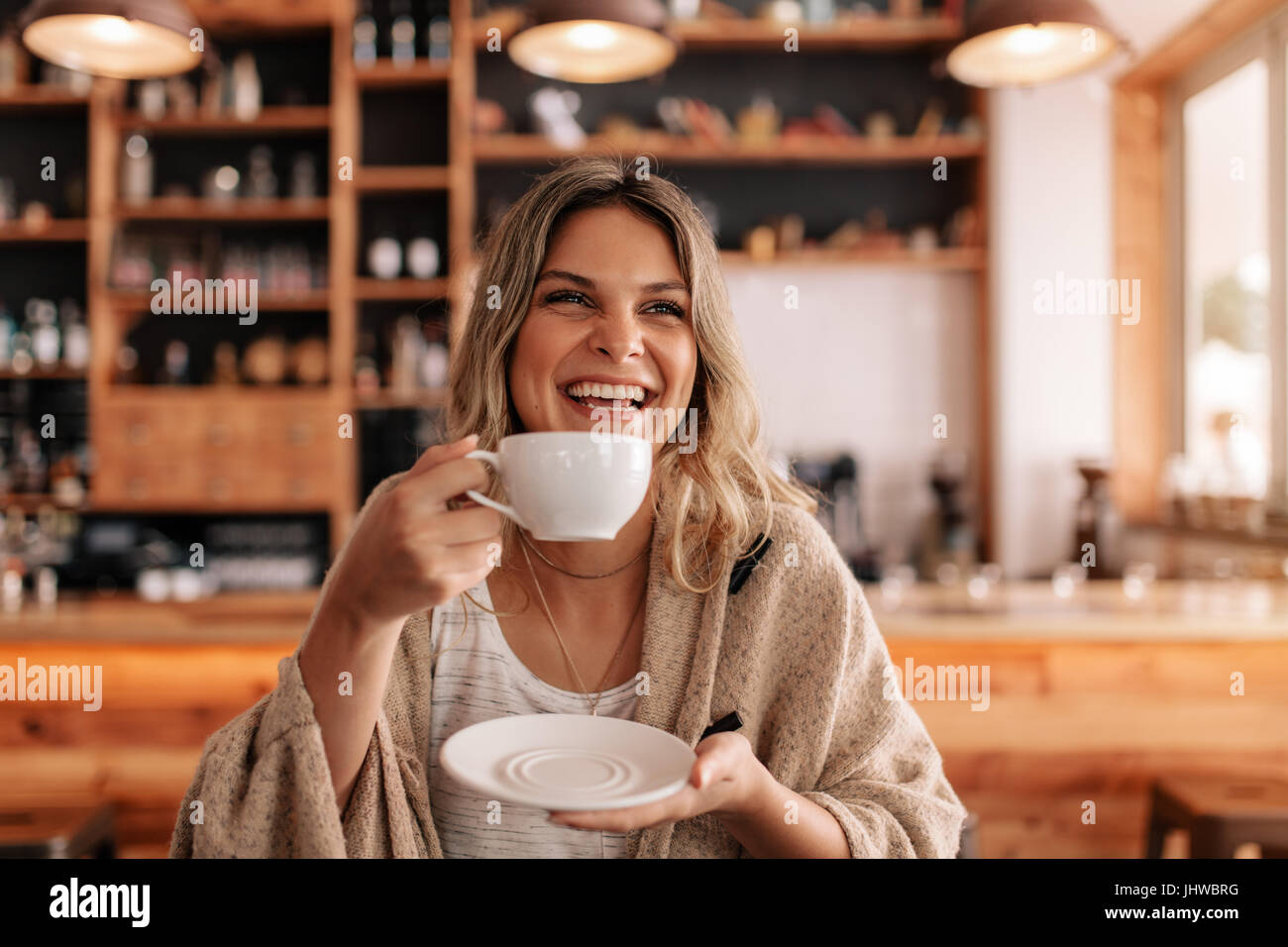 Portrait of beautiful young woman standing in a cafe and drinking coffee. Smiling young female having coffee in - Stock Image