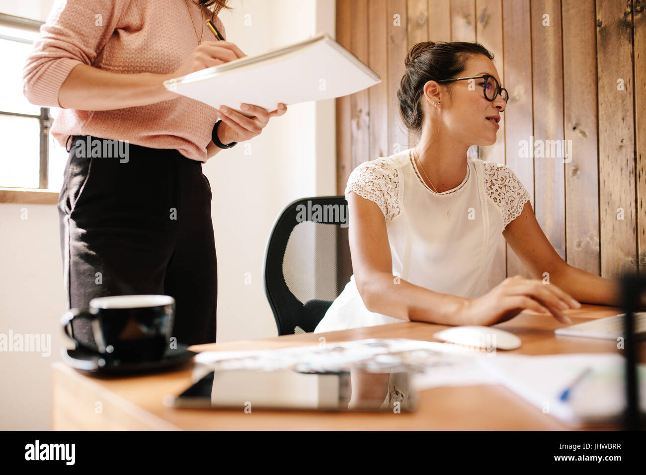 Business woman working at her desk with female colleague standing by with notepad. Two female office workers at - Stock Image