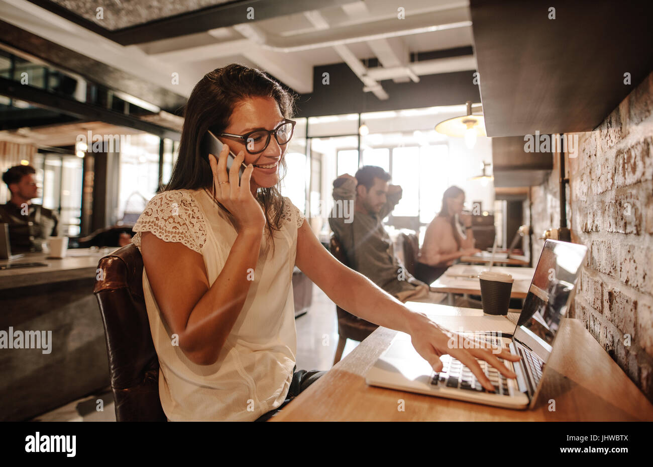 Happy businesswoman at office and talking on mobile phone. Casual businesswoman working at startup office. - Stock Image