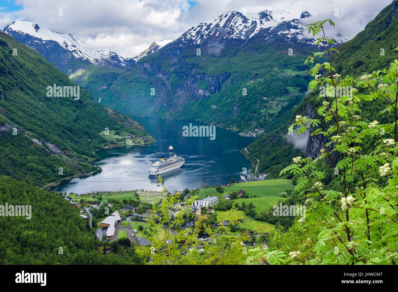 Scenic view to village at end of Geirangerfjorden fjord with cruise ships moored in summer. Geiranger Sunnmøre - Stock Image