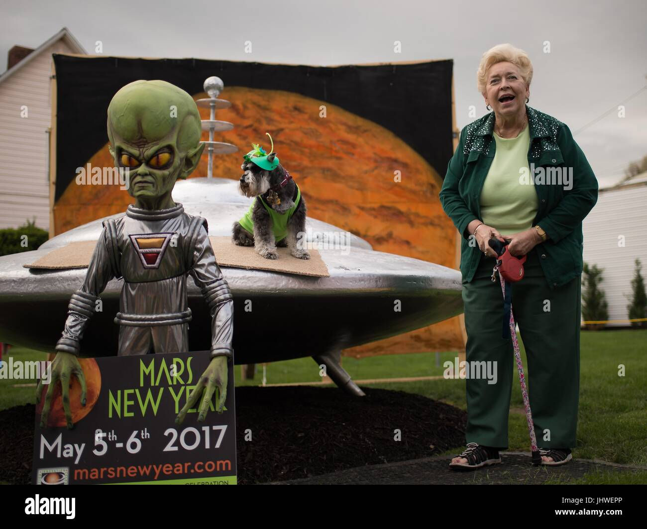Resident Sue Morris and her dog Pepper pose with a model spacecraft and alien during the NASA Mars New Year celebration - Stock Image