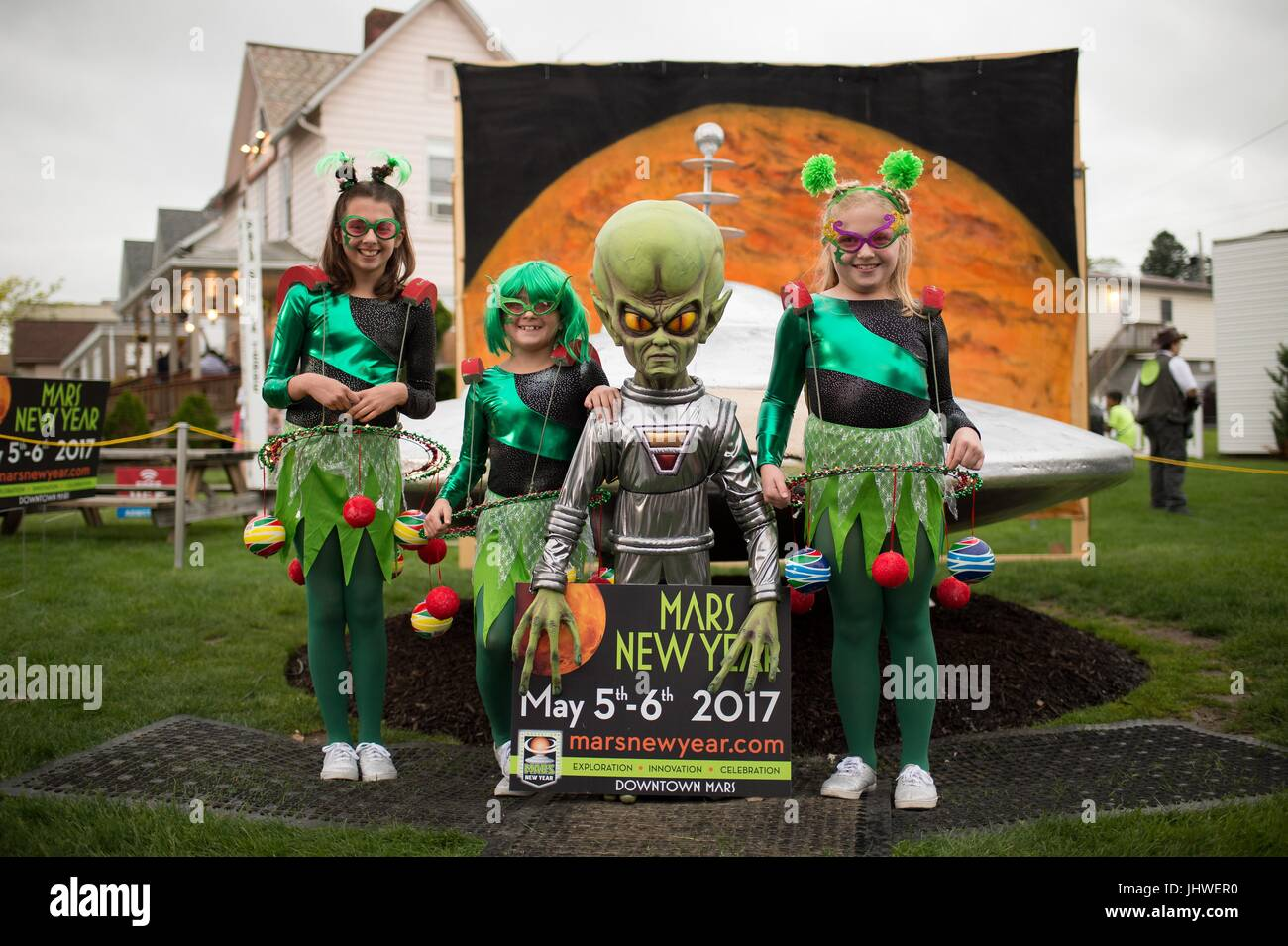 Children dressed in alien costumes pose with a model spacecraft and alien during the NASA Mars New Year celebration - Stock Image