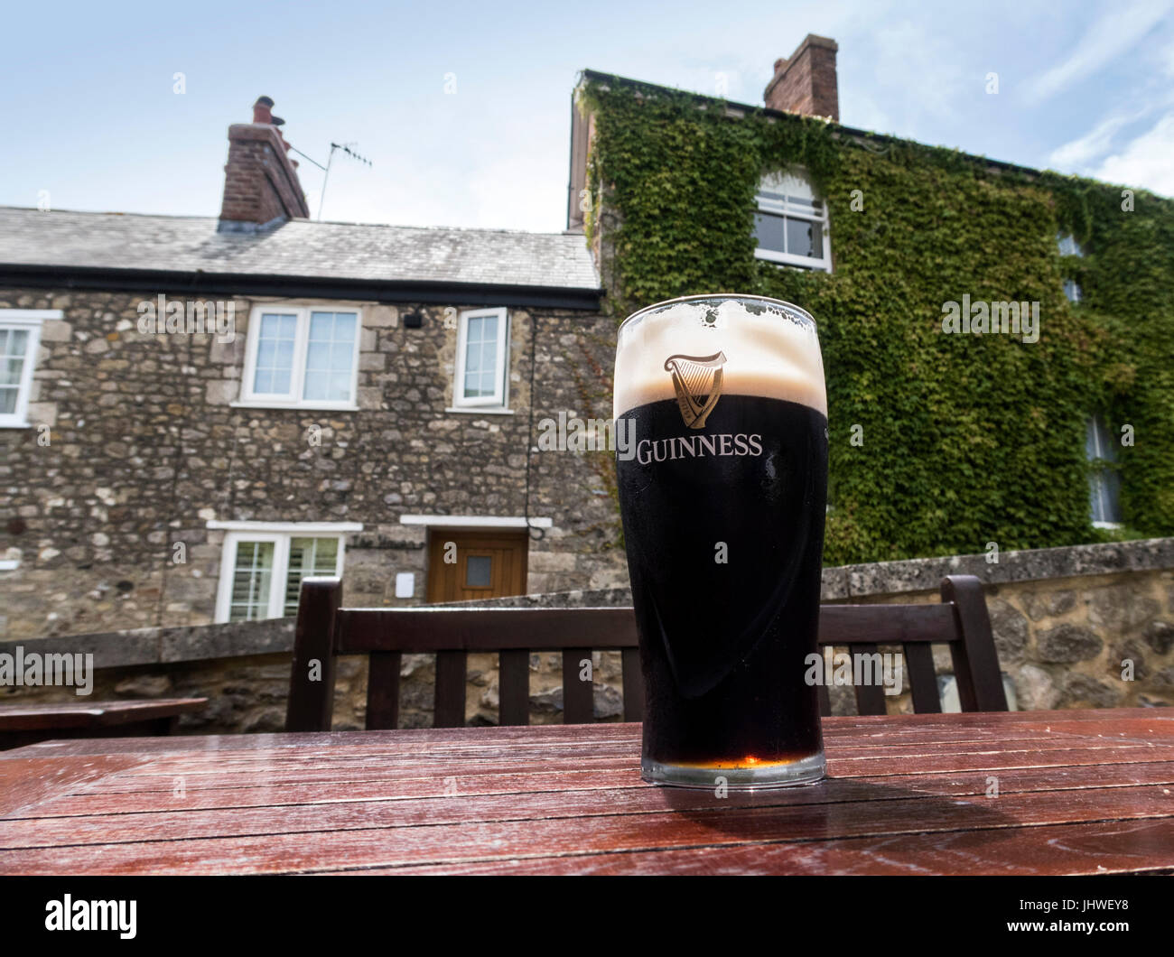 A pint of Guinness on a table outside a country pub. - Stock Image