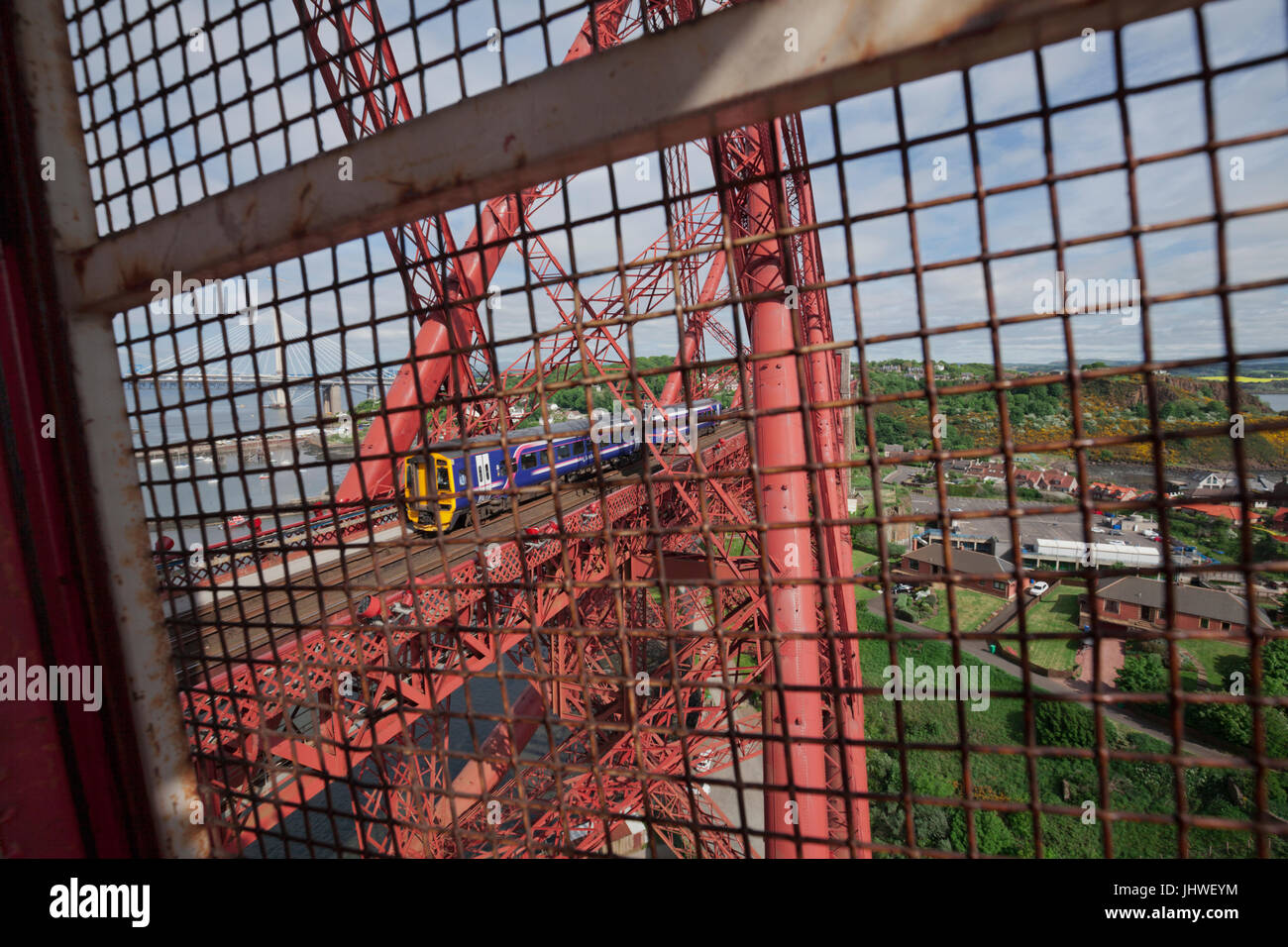The Forth Bridge (Fife) the 0934 Edinburgh - Perth  crosses, view from the lift heading to the top of the north - Stock Image