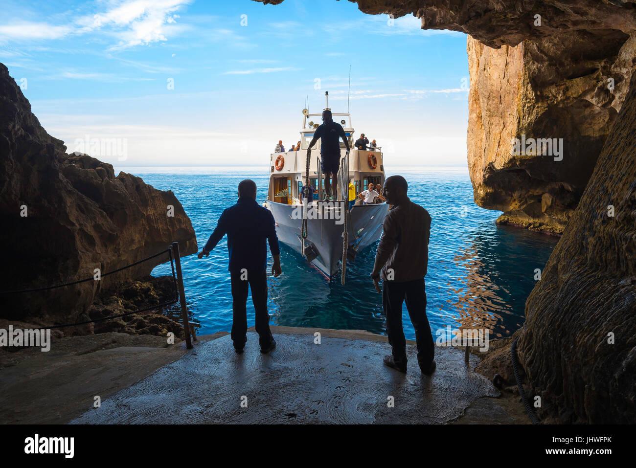 Sardinia coast tourism, two men prepare to dock a tour boat arriving at the Grotta di Nettuno at Capo Caccia near - Stock Image