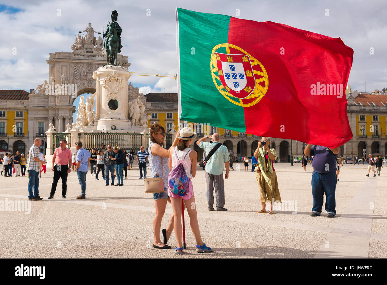 Lisbon city centre, in the Praca do Comercio tourists hold a large Portuguese flag while having their photo taken, - Stock Image