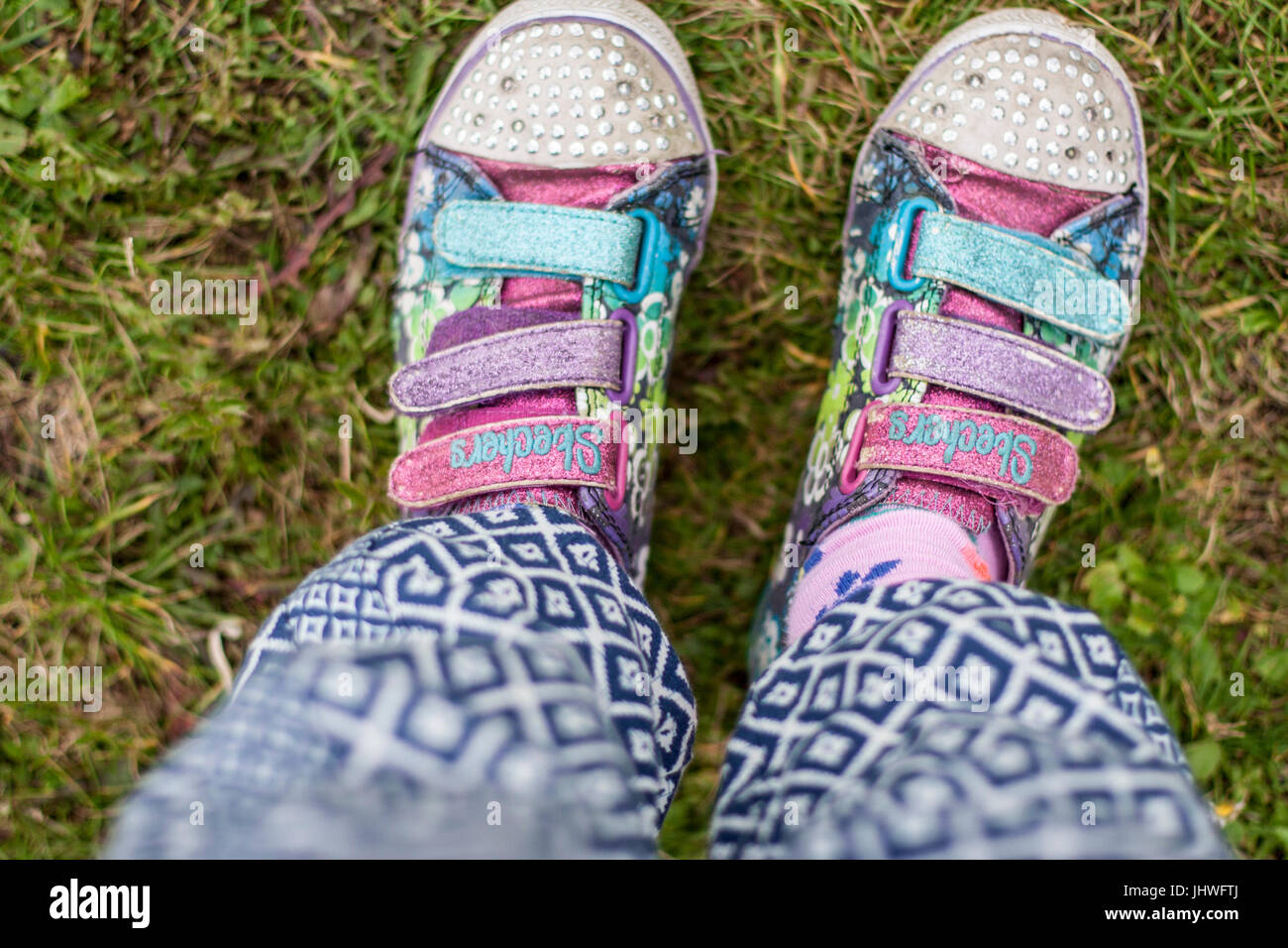 Childs feet in worn out well used shoes Sketchers - Stock Image