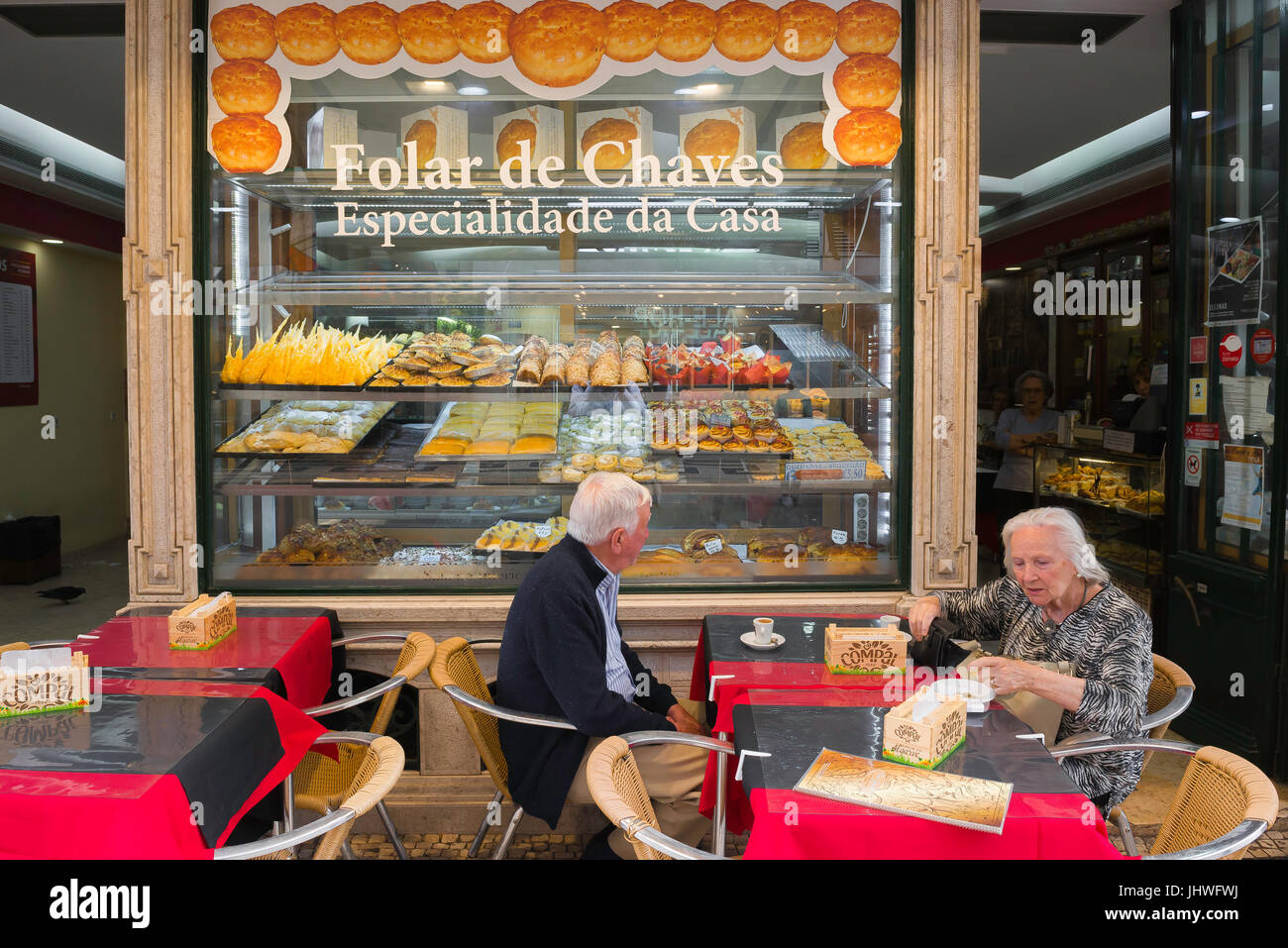 Lisbon Portugal food, two customers sit at a terrace outside a patisserie in the Rua Aurea in the historical centre - Stock Image