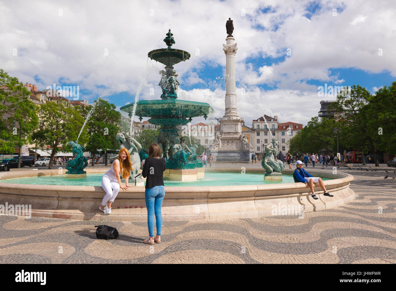 Lisbon city centre, a young woman sits on a fountain in the Praca Dom Pedro lV (Rossio) in Lisbon while her friend Stock Photo