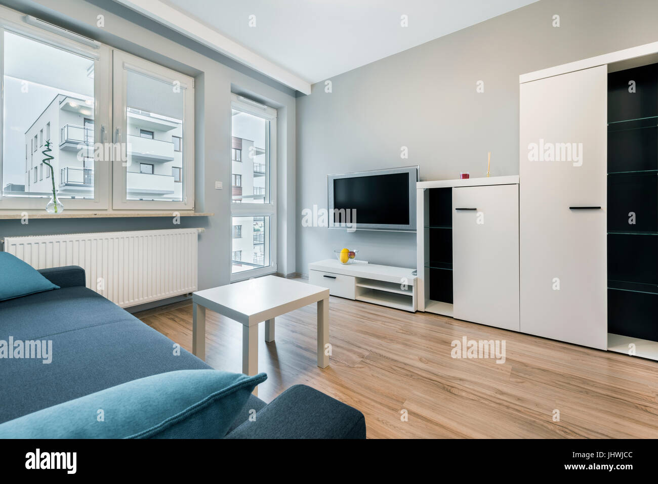 modern living room with grey walls and blue sofa stock photo